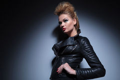 Woman in leather clothes standing with hands on hips and looking Royalty Free Stock Images