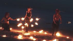 Woman in leather clothes and two men perform fire show at beach inside burning circle. Party stock video footage