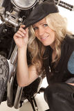Woman leather hat kneel by motorcycle smile Royalty Free Stock Photo