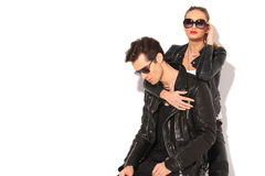 Woman in leather jacket embracing seated man from behind Stock Images