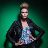 Woman in leather jacket and hands on hips is looking up Royalty Free Stock Images