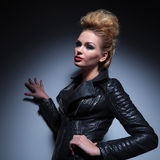 Woman in leather jacket leaning with one hand against a gray stu Royalty Free Stock Photos