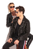 Woman in leather jacket is looking at her seated man Royalty Free Stock Image