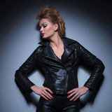 Woman in leather jacket is looking to her side and down Stock Photography