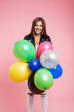 Woman in leather jacket posing with bunch of colored balloons Royalty Free Stock Image