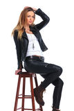 Woman in leather jacket posing in studio background while arrang Royalty Free Stock Photography