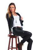 Woman in leather jacket posing in studio background while seate Royalty Free Stock Image