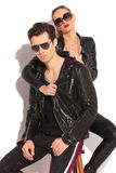 Woman in leather jacket pulling  collar of her seated man Stock Photos