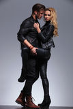 Woman in leather jacket is pulling her man closer. Young sexy women in leather jacket is pulling her men closer and looks at the camera Stock Image