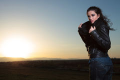 Woman in leather jacket and scarf looking away in the dusk Royalty Free Stock Photo