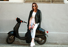 Woman in leather jacket on scooter on background gray wall Stock Photo