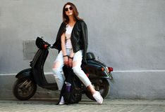 Woman in leather jacket on scooter on background gray wall Royalty Free Stock Photography