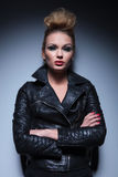Woman in leather jacket standing with arms crossed. Serious fashion woman in leather jacket standing with arms crossed against gray studio background Royalty Free Stock Photo