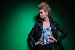 Woman in leather jacket standing with hands on hips and looking Stock Image