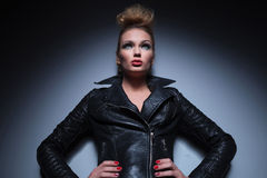 Woman in leather jacket standing with hands on hips and looking Royalty Free Stock Photo