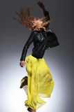 Woman in leather jacket and yellow dress making a jump Royalty Free Stock Photography