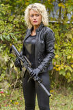 Woman in leather with machine gun Stock Images