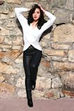 Woman in leather pants. Picture taken outside woman against stone wall black leather pats Royalty Free Stock Images