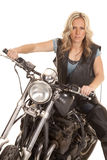 Woman leather vest sit on motorcycle look serious Royalty Free Stock Image