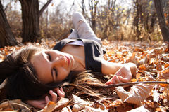 Woman on leaves. Young woman lays on autumn leaves Stock Photo