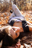 Woman on leaves. Young woman lays on autumn leaves Stock Photos