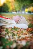 Woman in leaves. Young woman having fun and lying in the fall leaves Stock Image