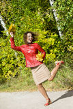 Woman with leaves in hands in jump in autumn Royalty Free Stock Images
