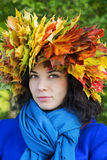 Woman with leaves on head look straight. Woman with maple leaves on head look straight Royalty Free Stock Images