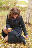 Woman with leaves on the street in autumn royalty free stock image