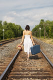 Woman Leaving. A back view of a young woman leaving with suitcase, hat and the clothes on her back stock photo