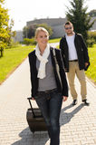 Woman leaving with baggage man walk behind Royalty Free Stock Photography