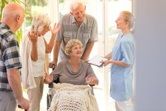Woman leaving hospital. Young nurse saying goodbye to elder women leaving hospital with her siblings stock photo