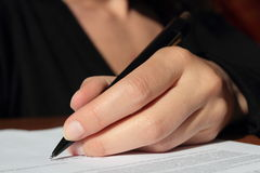 Woman left hand signing contract writing text Royalty Free Stock Photos