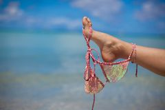 Woman leg hold pink bra isolated on exotic Stock Photo