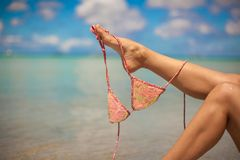 Woman leg holding pink bra isolated on exotic Royalty Free Stock Photo