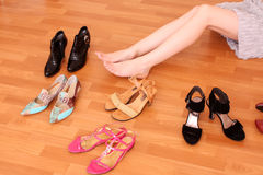 Woman leg and many shoes around. Closeup of a woman leg on floor and many shoes around stock image