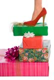 Woman leg in red shoe on pile of birthday Gifts. Female Leg in red shoe standing on stack of wrapped christmas gifts Royalty Free Stock Photo