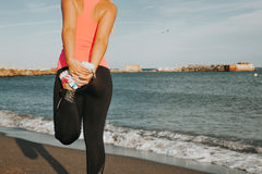 Woman leg stretching at the beach. stock photography