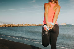 Woman leg stretching at the beach. stock image