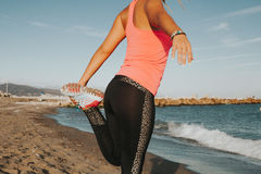 Woman leg stretching at the beach. Stretching legs and quadriceps during running workout. Woman backs royalty free stock photo
