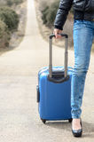 Woman Leg with Suitcase and Lonely Road. Stock Image