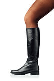 Woman leg wearing black leather high boot Royalty Free Stock Image