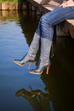 Woman legs above water. Woman legs in blue jeans and boots above water Stock Photography