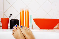 Woman legs in bathroom with lot of stylish stuff for care, pedicure creative design, hygiene concept Royalty Free Stock Images