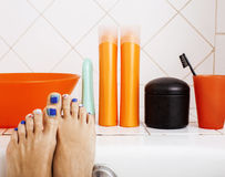 Woman legs in bathroom with lot of stylish stuff for care, pedicure creative design, hygiene concept Royalty Free Stock Image