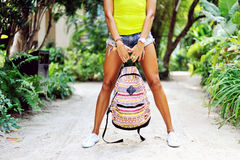 Woman legs. Beautiful female holding bag wearing jeans shorts an. D sneakers Stock Photos