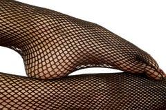 Woman legs black fishnet close foot on leg Stock Photos