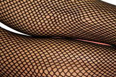 Woman legs black fishnet close one over the other Royalty Free Stock Photos