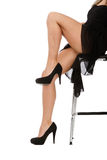 Woman legs and black heels in white background. And high chair Royalty Free Stock Photography