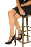 Woman legs black skirt and heels sit Stock Photo